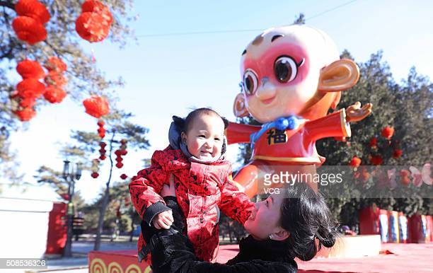 People play at the Temple of Earth Park where a giant monkey mascot is decorated for the upcoming Spring Festival on February 4 2016 in Beijing China...
