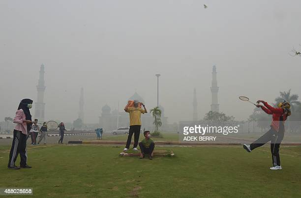 People play badminton while wearing face masks in the grounds of the AnNur Great Mosque as haze shrouds the Sumatran city of Pekanbaru in Riau...