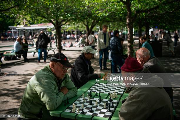 People play chess at a park in Stockholm on May 29 amid the coronavirus COVID-19 pandemic. - Sweden's two biggest opposition parties called Friday...