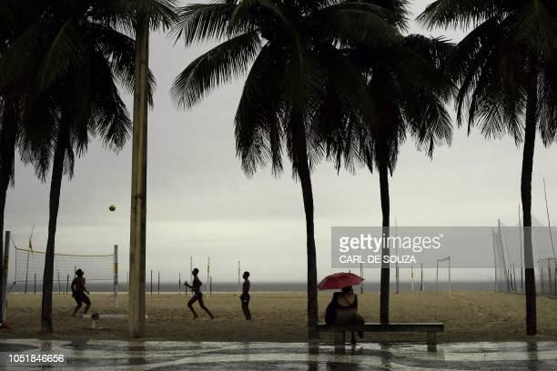 TOPSHOT People play football under the rain in Copacabana beach on October 10 2018