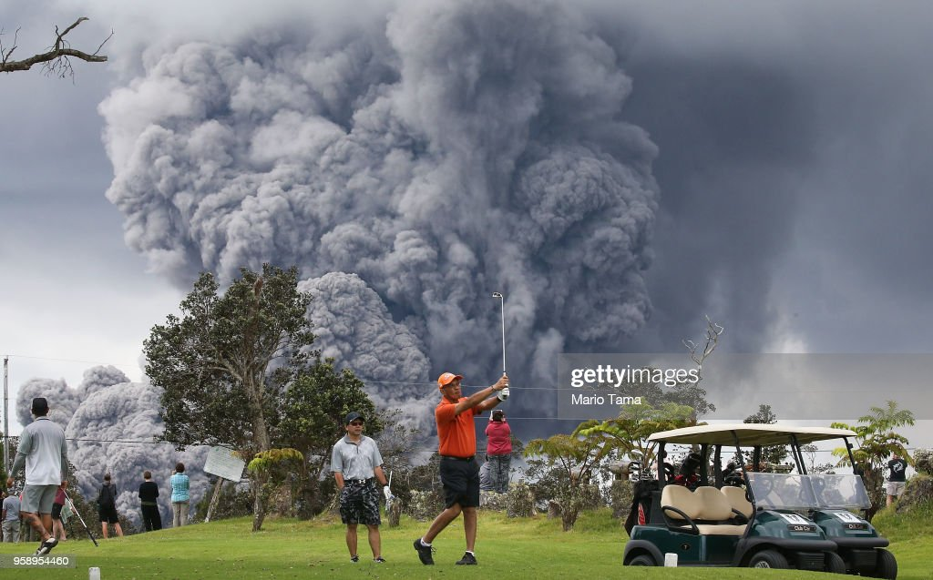 People play golf as an ash plume rises in the distance from the Kilauea volcano on Hawaii's Big Island on May 15, 2018 in Hawaii Volcanoes National Park, Hawaii. The U.S. Geological Survey said a recent lowering of the lava lake at the volcano's Halemaumau crater 'has raised the potential for explosive eruptions' at the volcano.