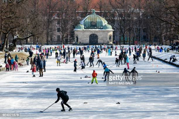 People play ice hockey on the frozen canal at Nymphenburg Palace in Munich, southern Germany, on February 25, 2018. / AFP PHOTO / dpa / Matthias Balk...