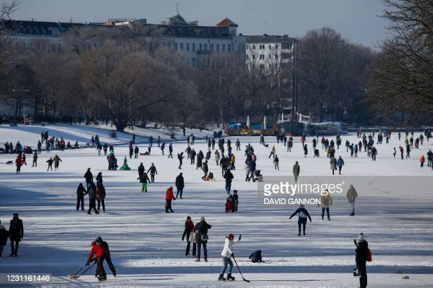 People play Ice Hockey, skate and walk on the frozen Landwehr Canal in Berlin's Kreuzberg district on February 14, 2021.