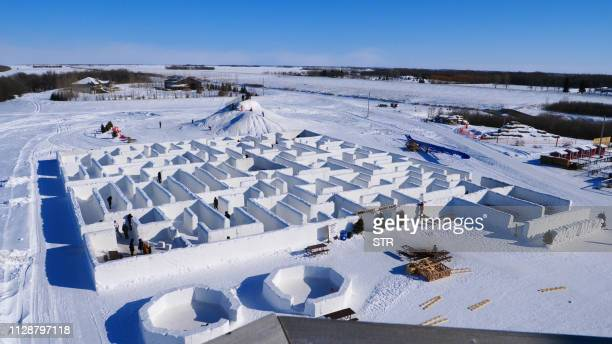 TOPSHOT People play in a maze built by farmers Clint and Angie Masse in St Adolphe Canada on March 3 2019 The snow labyrinth in the frigid windswept...