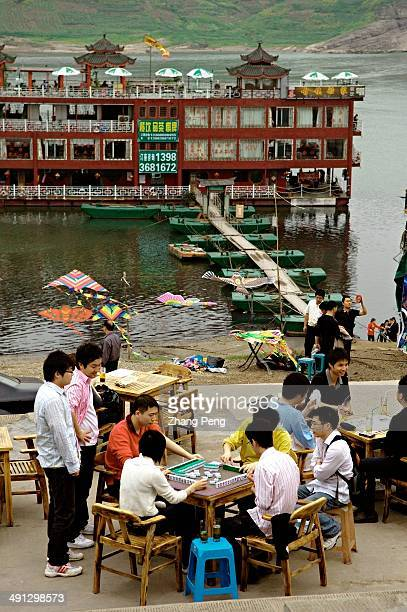 People play Mahjong while drinking tea in an openair tea shop beside a river in Chongqing which is famous as a leisure city in southwest China