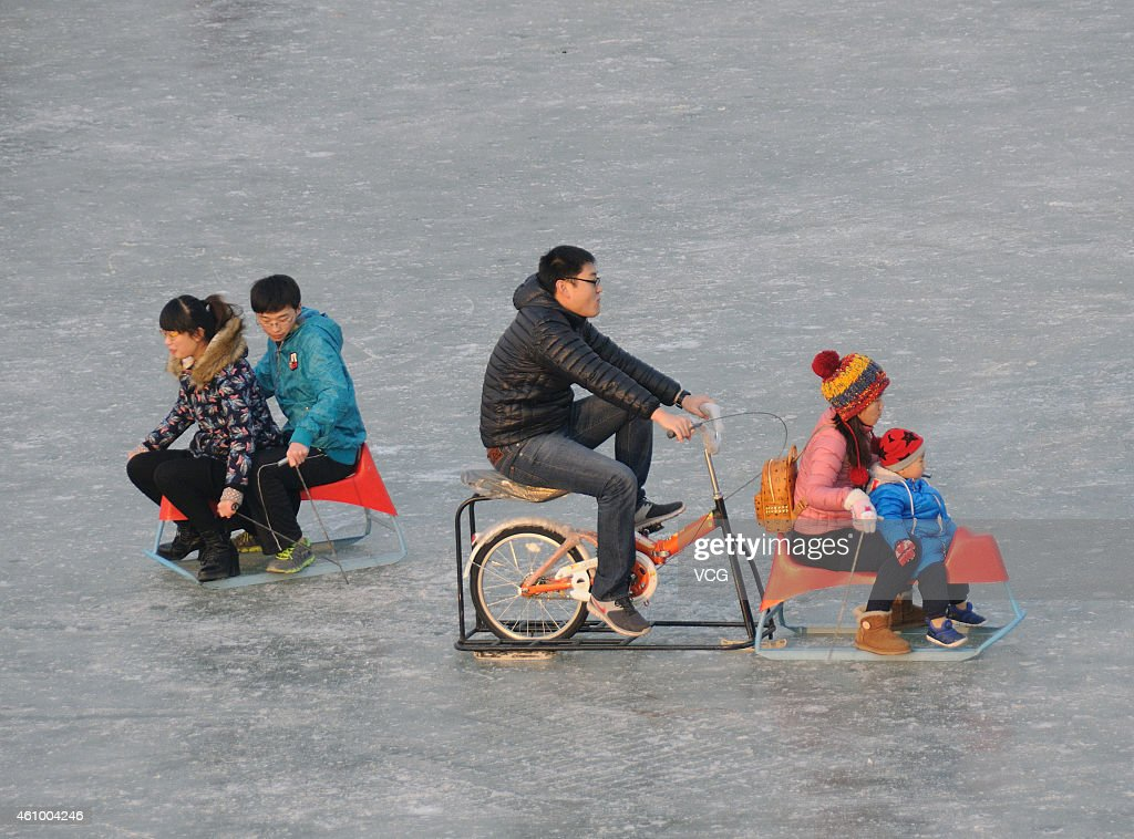 People play on a frozen Kunming Lake at the Summer Palace on January 3, 2015 in Beijing, China.