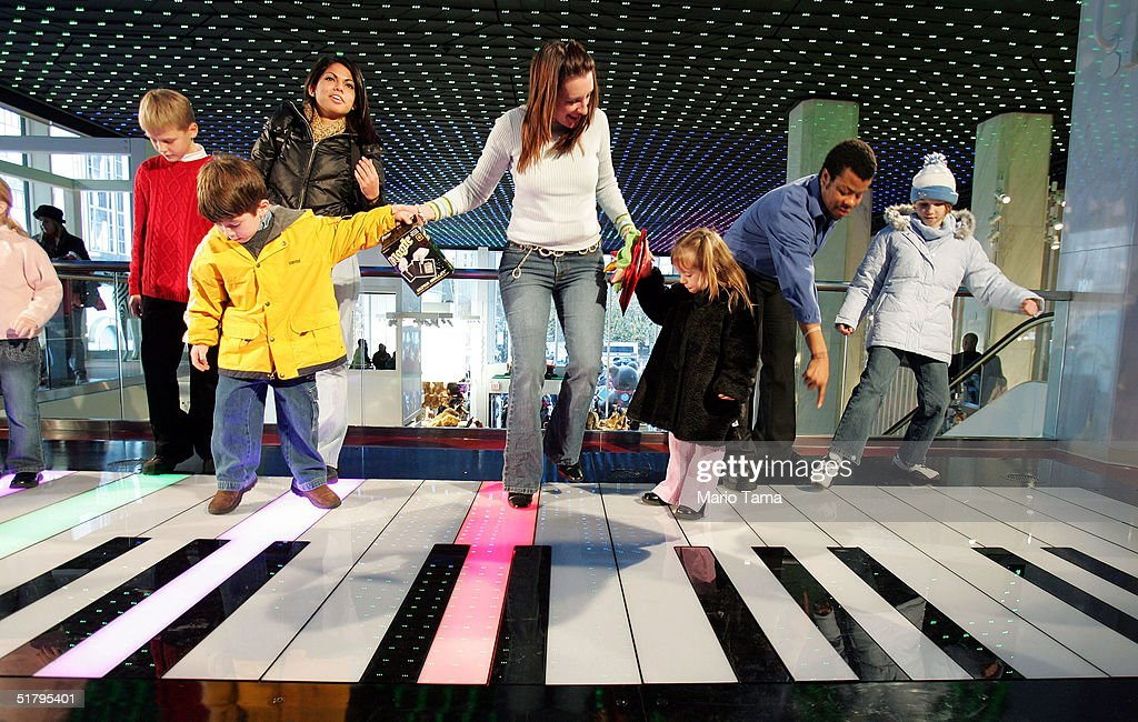People play on a giant keyboard inside FAO Schwarz, the day after its grand re-opening November 26, 2004 in New York City. The Friday after Thanksgiving, called 'Black Friday,' is one of the busiest shopping days of the year with stores opening early and a large number of shoppers looking for holiday gifts.