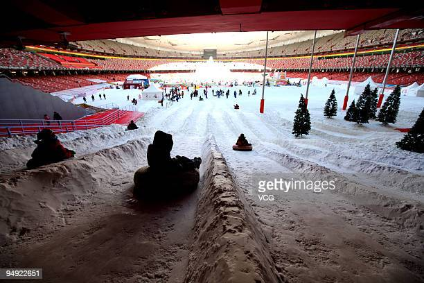 People play on artificial snow inside China's iconic national stadium also known as the Bird's Nest on the opening day of the 'Winter Playground'...