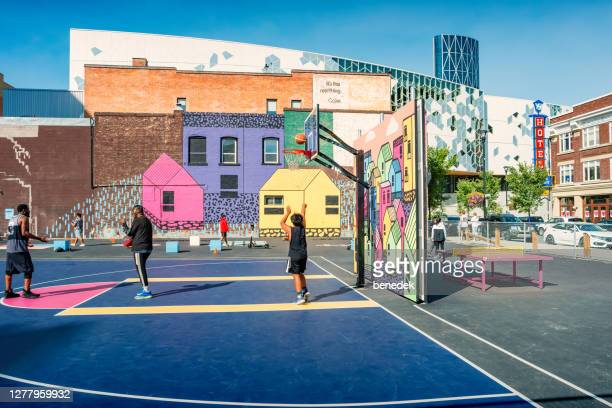 people play on basketball court downtown calgary alberta canada - calgary stock pictures, royalty-free photos & images