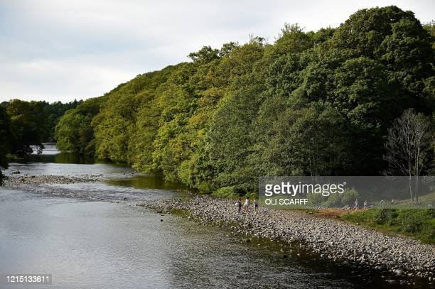 People play on the bank of the River Tees at Barnard Castle less than 30 miles southwest of Durham north east England on May 25 a popular tourist...