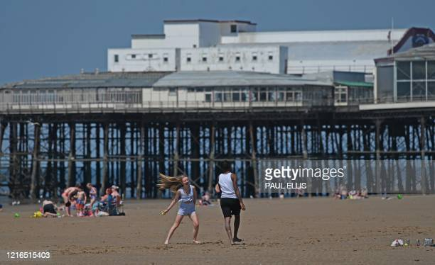 People play on the beach in the warm sunshine in Blackpool on the northwest coast of England on May 31 2020 on the eve of a further relaxation of the...