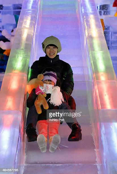"""People play on the ice slide at """"Fantasy Ice World"""" on January 23, 2014 in Taipei, Taiwan. Ice sculptors from the famous Harbin Ice Festival create..."""