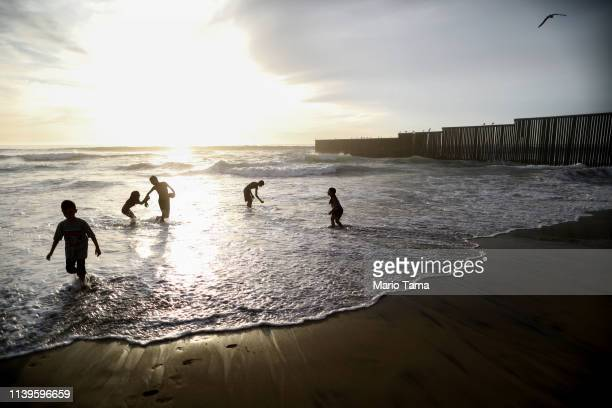 People play on the USMexico border on the beach with the border barrier in the background on March 31 2019 in Tijuana Mexico US President Donald...
