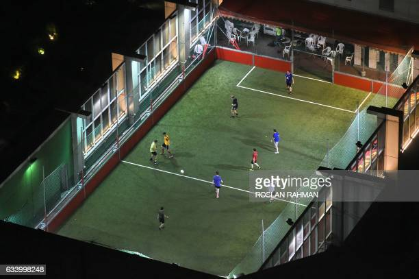 People play street soccer popularly known as futsal on a highrise pitch in the outskirts of Singapore's central business district on February 6 2017...