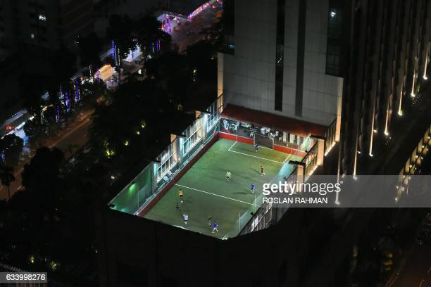 TOPSHOT People play street soccer popularly known as futsal on a highrise pitch in the outskirts of Singapore's central business district on February...