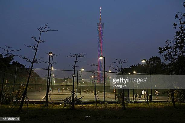 People play tennis for exercise as the Canton Tower rise in the distance at night on March 26 2014 in Guangzhou China