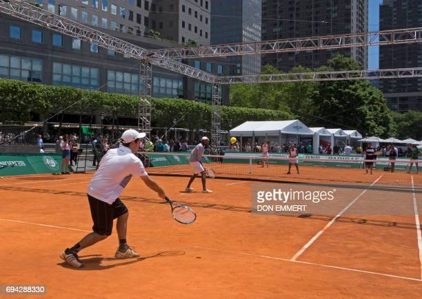 People play tennis on a clay court at RolandGarros in the City an outdoor restaurant in New York's Battery Park June 9 where French Open matches of...