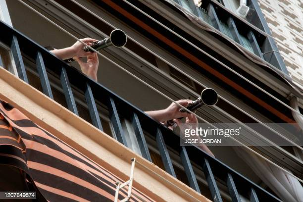 People play the clarinet from their balcony during home confinement due to the novel coronavirus on March 19 2020 in Valencia Spain announced deaths...