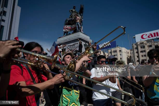 People play their musical instruments during a demonstration at Plaza Italia in Santiago on the fifth straight day of street violence which erupted...