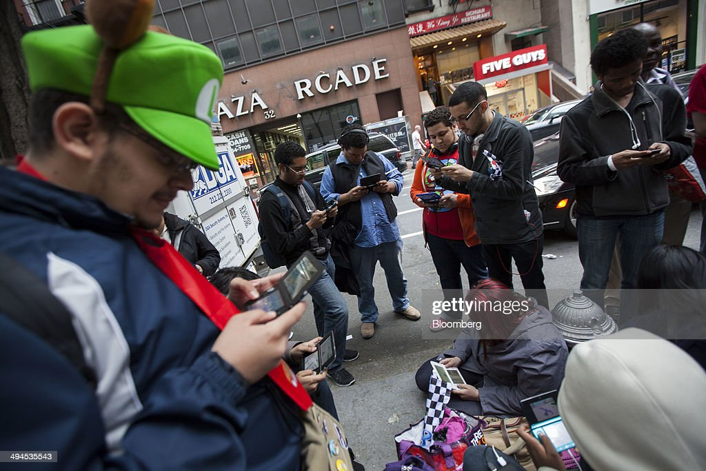 People play video games while waiting in line for the Mario