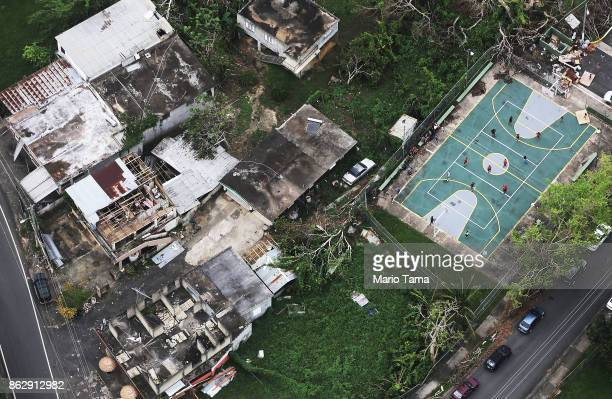 People play volleyball next to damaged buildings during recovery efforts four weeks after Hurricane Maria struck on October 18, 2017 in-flight over...