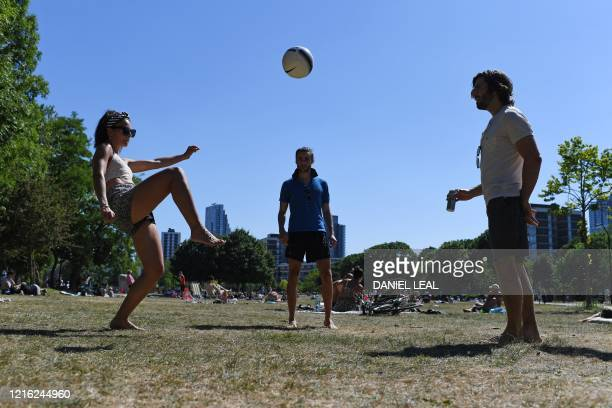 People play with a football as they enjoy the sunny weather in Shoreditch Park in London on May 30 ahead of the coming into force of the first...