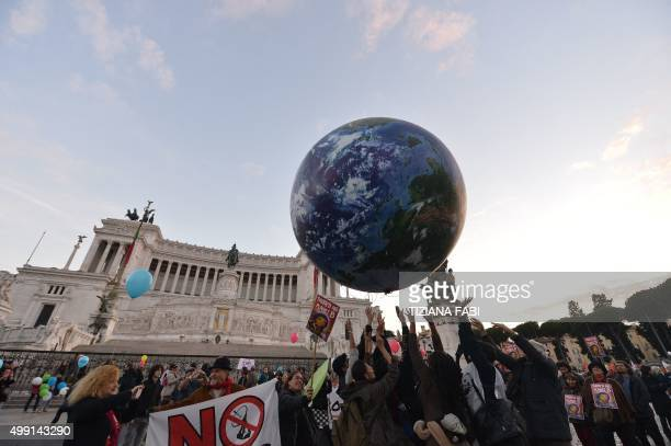 People play with a giant balloon representing Earth at Piazza Venezia during a rally calling for action on climate change on November 29 2015 in Rome...