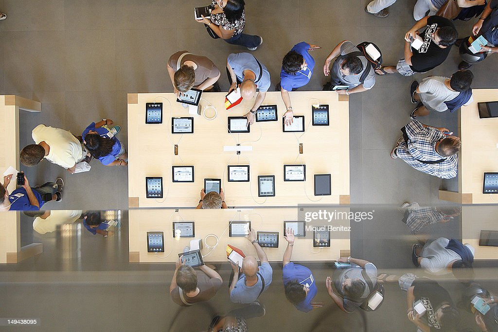 People play with Apple items as they attend the opening of Apple's New Barcelona Store in Passeig de Gracia on July 28, 2012 in Barcelona, Spain.