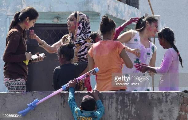 People play with colours during Holi celebrations at Gandhi Nagar on March 10 2020 in New Delhi India