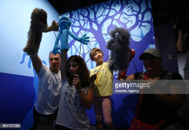 People play with puppets characters of the famous TV serie Sesame Street is displayed during an exhibition in memory of American puppeteer and movie...