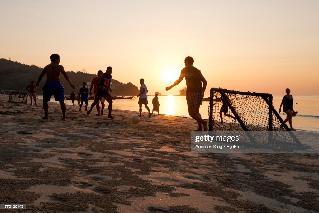 People Playing At Beach Against Sky During Sunset : Photo