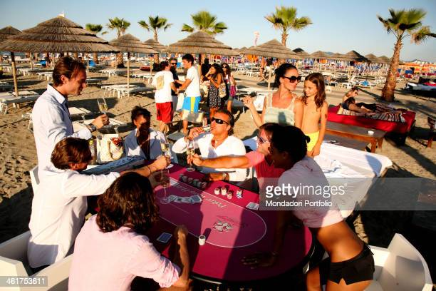 People playing cards during a photo shooting at the lido Flamingo Beach Riccione Italy 10th July 2009