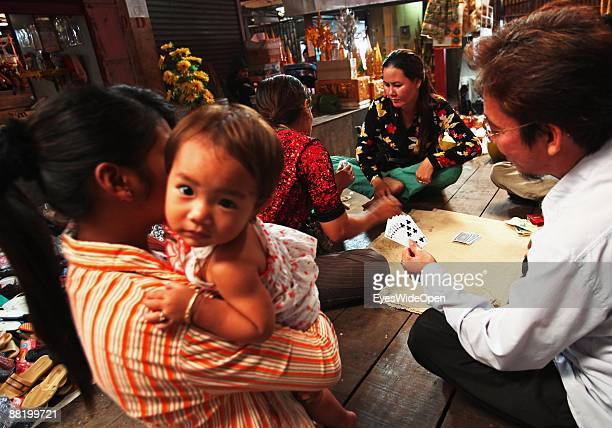 People playing cards on a marketplace in Siem Reap where Tourists take part in a cooking course to learn how to cook the traditional Fish Amok on...