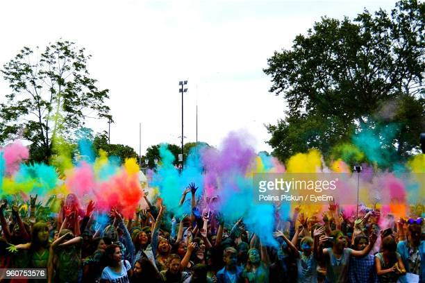 People Playing Colorful Powder Paint While Standing Against Sky