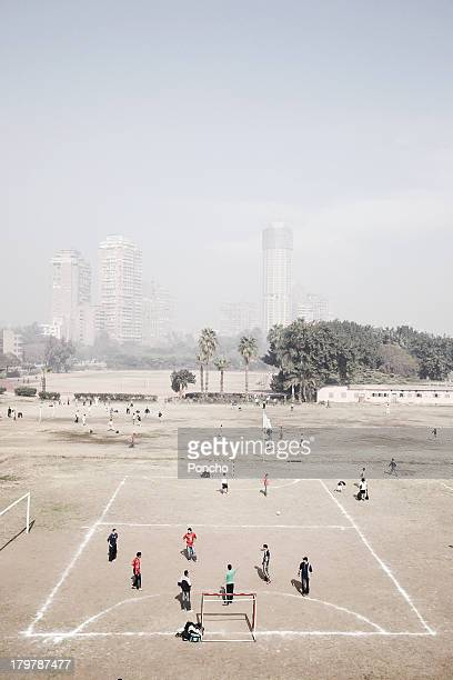 People playing football in front of Cairo skyline