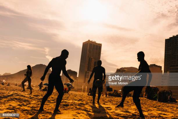 people playing football on copacabana beach, rio de janeiro - famous footballers silhouette stock pictures, royalty-free photos & images