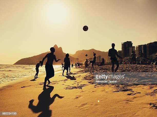 people playing football on ipanema beach in rio - río de janeiro fotografías e imágenes de stock