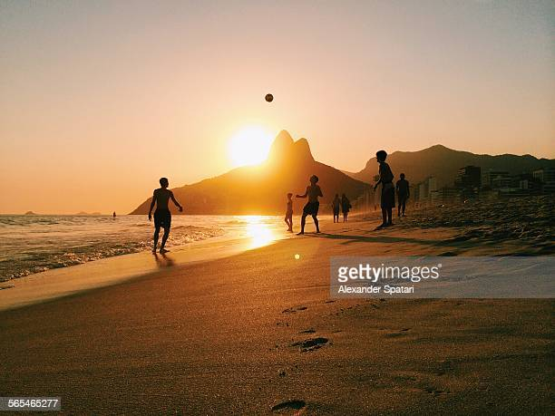 people playing football on ipanema beach in rio - rio de janeiro stock-fotos und bilder