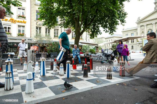 people playing lifesize chess on street in old town of bern, switzerland - life size stock pictures, royalty-free photos & images