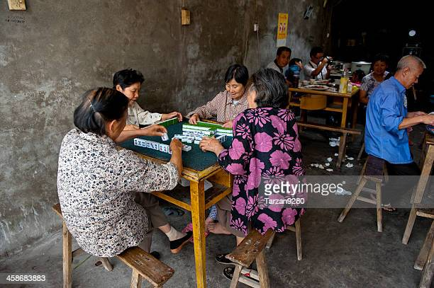 people playing mahjong inside dark teahouse - mahjong stock photos and pictures