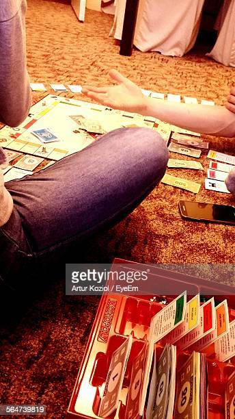 people playing monopoly board game at home - monopoly board game stock pictures, royalty-free photos & images