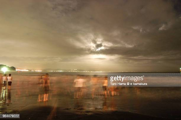People playing on the night beach after the fireworks festival in Enoshima Island in Japan