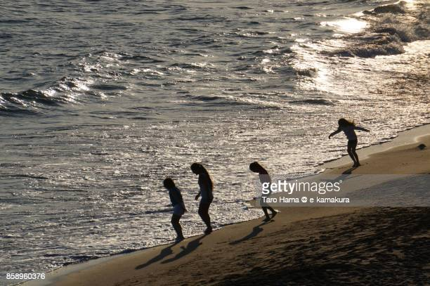 People playing on the sunset beach in Kamakura city in Kanagawa prefecture in Japan
