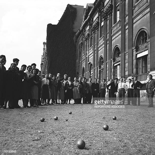 People playing petanque in front of the Louvre museum in Paris France in 1950's