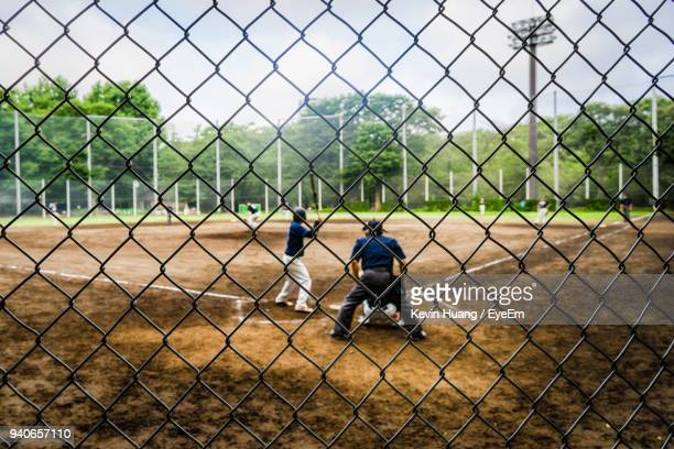 people playing seen through chainlink fence - bate de béisbol fotografías e imágenes de stock