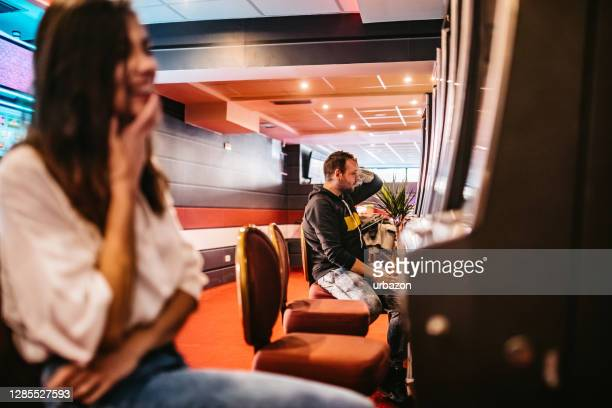 people playing slot machine in casino - defeat stock pictures, royalty-free photos & images