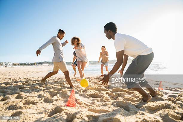 People playing soccer at the beach