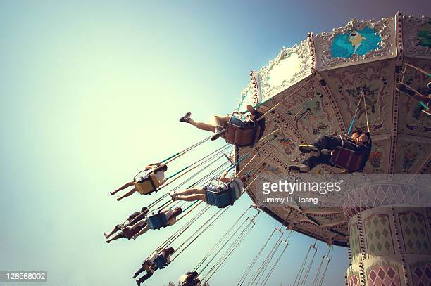 People playing swing carousel in amusement park
