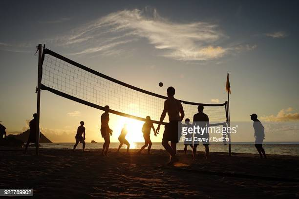 people playing volleyball at beach against sky during sunset - beachvolleybal stockfoto's en -beelden