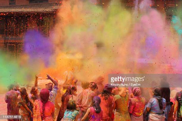 people playing with powder paint during holi in city - holi stock pictures, royalty-free photos & images